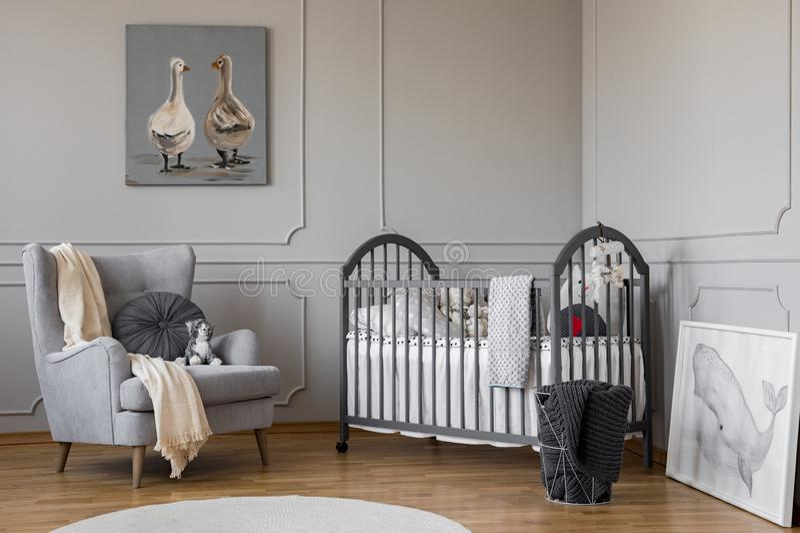 Comfortabele grijze leunstoel met rond hoofdkussen en witte deken naast houten voederbak met hoofdkussens en speelgoed, exemplaar stock fotografie