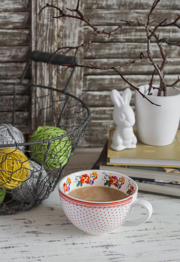 Comfortabele huiszetel met een mand met garen, gestapelde boeken, vaas met droge takken, een ceramisch konijn en een Kop thee met stock fotografie