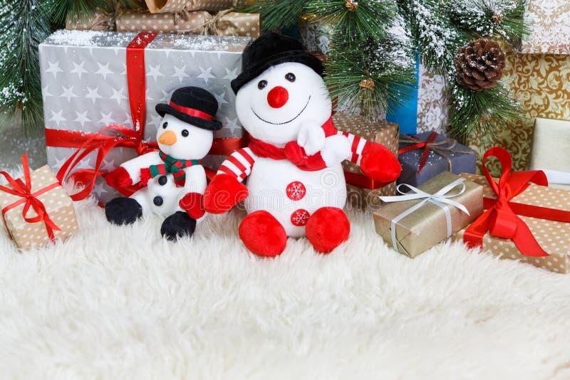 Comfortabele Kerstmisachtergrond Stuk speelgoed de sneeuwmannen en stelt onder nieuwe jaarboom voor stock afbeeldingen