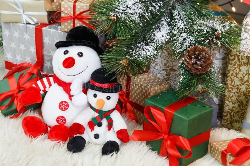Comfortabele Kerstmisachtergrond Stuk speelgoed de sneeuwmannen en stelt onder nieuwe jaarboom voor stock afbeelding