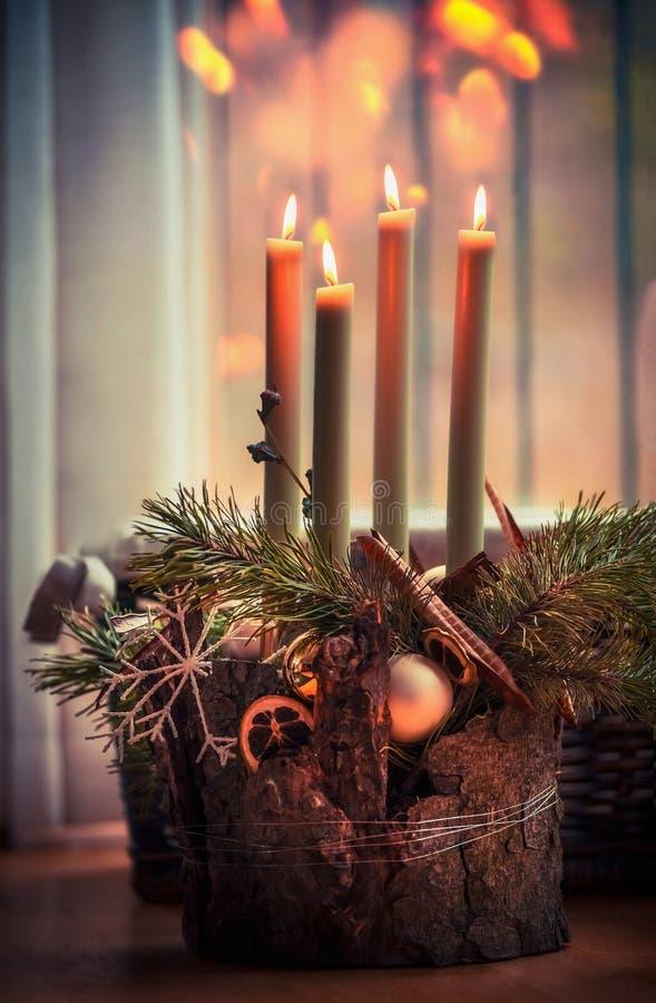 Comfortabele Kerstmistijd thuis Komstkroon met vier brandende kaarsen Het binnenland van het de winterdecor met warme bokehverlic stock fotografie