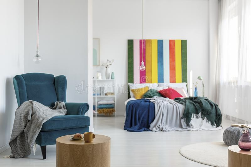 Comfortabele leunstoel met grijze deken in kleurrijke slaapkamer met het bed van de koningsgrootte en multicolored hoofdeinde stock foto