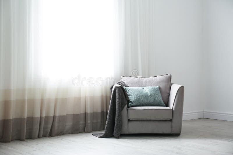 Comfortabele leunstoel met hoofdkussens en plaid dichtbij venster Binnenlands ontwerp stock afbeelding
