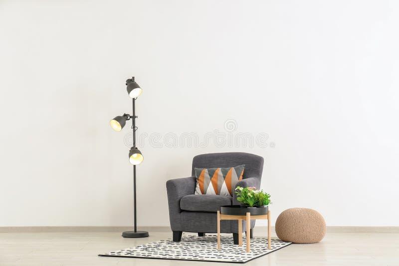 Comfortabele leunstoel met lijst, poef en staande lamp dichtbij lichte muur stock afbeelding