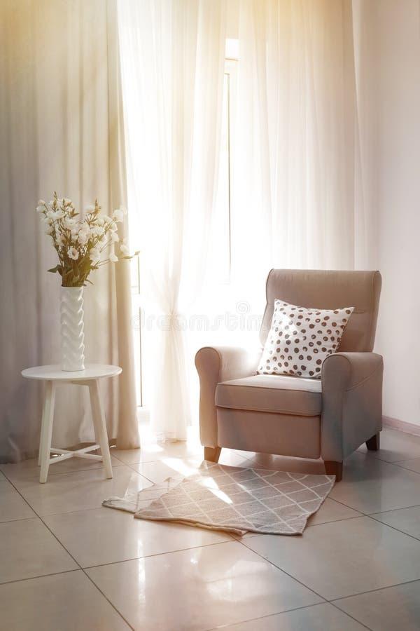 Comfortabele leunstoel voor rust met mooie bloemen in vaas dichtbij venster royalty-vrije stock foto's