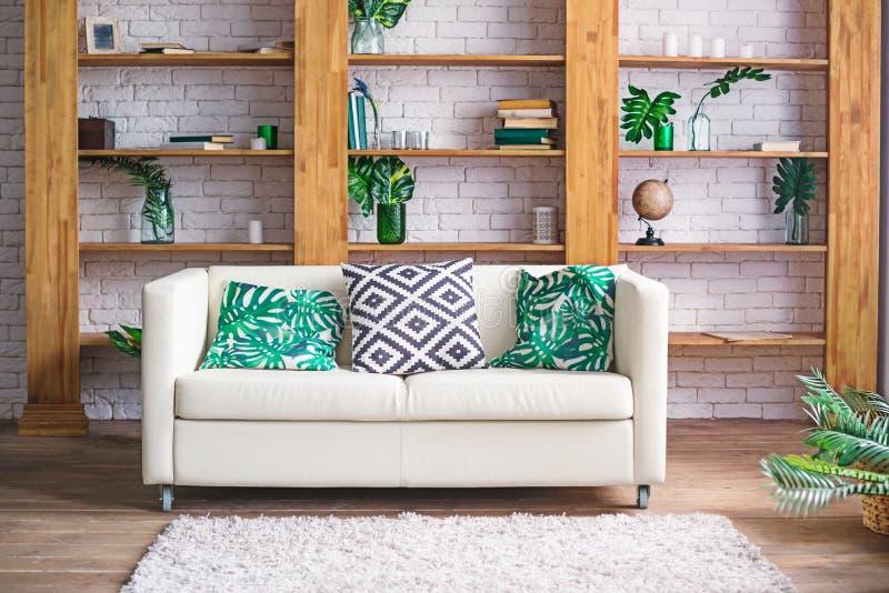 Comfortabele lichte ruimte met installaties, witte bank en modieus meubilair in Skandinavische stijl Woonkamer binnenlands concep royalty-vrije stock foto