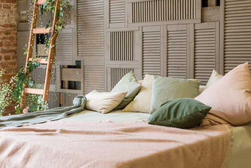 Comfortabele pastelkleurenslaapkamer met bruine houten muur en eenvoudig houten meubilair in minimalistische stijl de hoofdkussen stock afbeelding