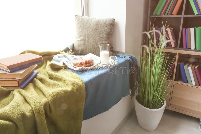 Comfortabele plaats voor rust met boeken en smakelijk ontbijt op vensterbank stock afbeeldingen