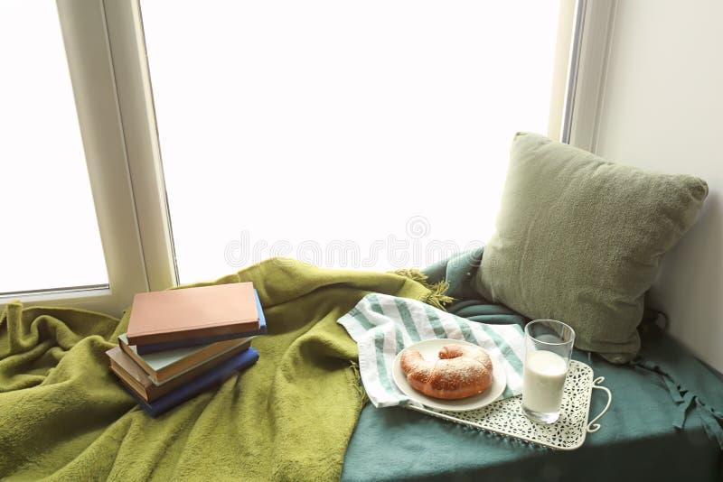 Comfortabele plaats voor rust met boeken en smakelijk ontbijt op vensterbank royalty-vrije stock foto