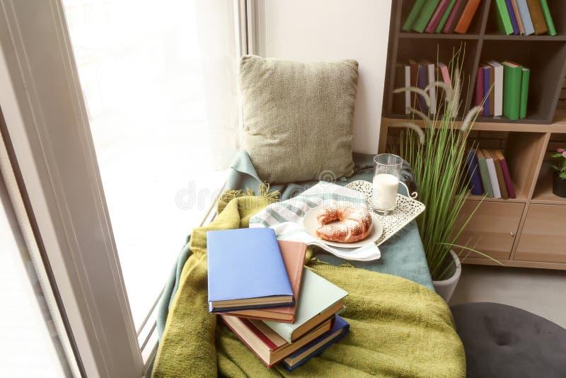 Comfortabele plaats voor rust met boeken en smakelijk ontbijt op vensterbank royalty-vrije stock afbeelding