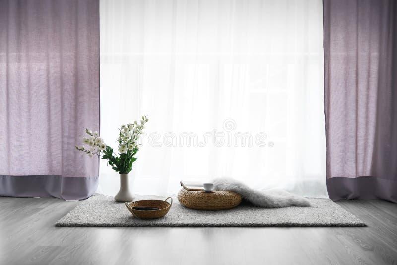 Comfortabele plaats voor rust met kop thee en boeken dichtbij venster stock foto's