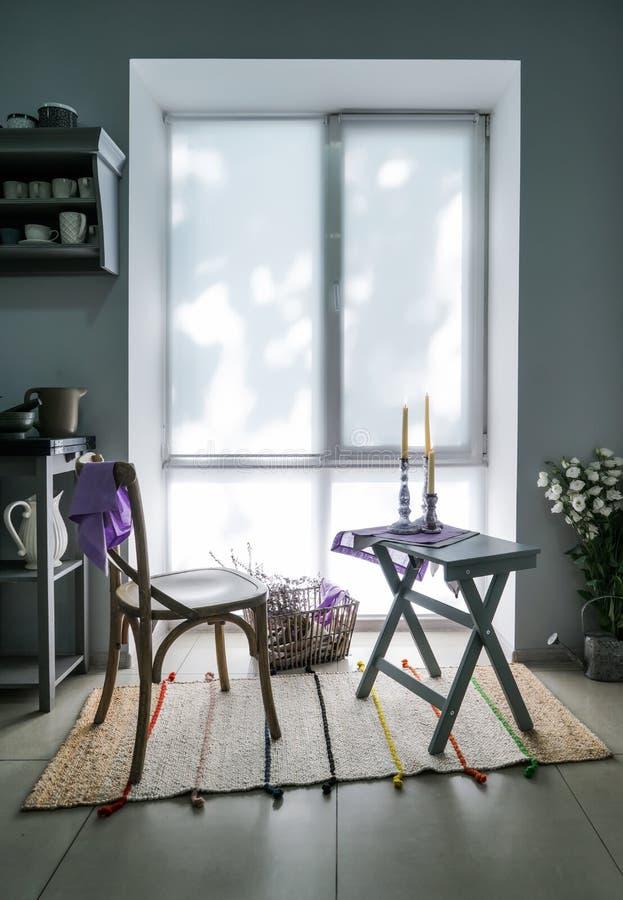 Comfortabele plaats voor rust met stoel en lijst dichtbij venster in keuken stock foto's