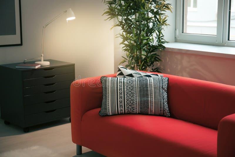 Comfortabele rode bank met hoofdkussens stock foto