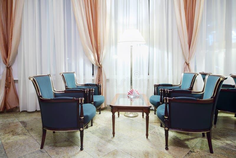 Comfortabele ruimte met lijst en groene stoelen en grote vensters royalty-vrije stock foto