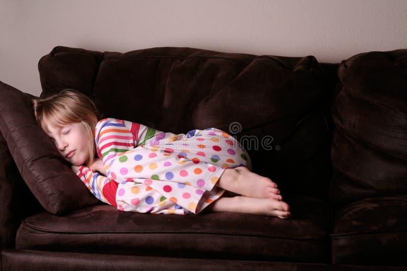 Comfortabele in slaap in pyjama's op bank stock fotografie