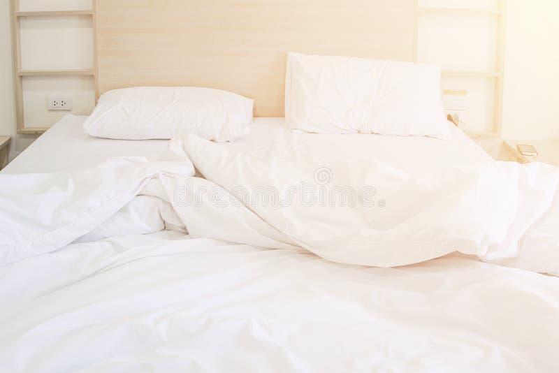 Comfortabele slordige slaapkamer onopgemaakte witte bedsheet en hoofdkussen na slaap met zonlicht in het ochtendeffect stock foto's