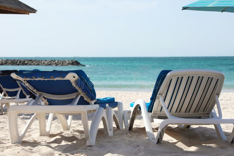 Comfortabele sunbeds op zandig strand stock fotografie
