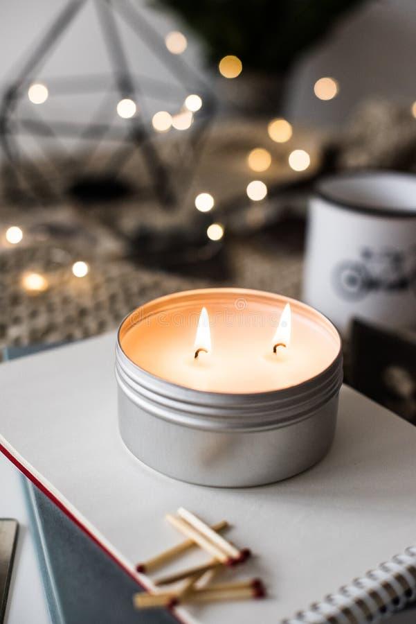 Comfortabele warme huisdecoratie met het branden van kaars en bokeh lichten stock foto's