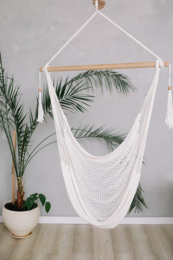 Comfortabele witte hangmat op het leven gebied, ontspannende hoek met palm thuis Minimaal huis binnenlands ontwerp stock fotografie