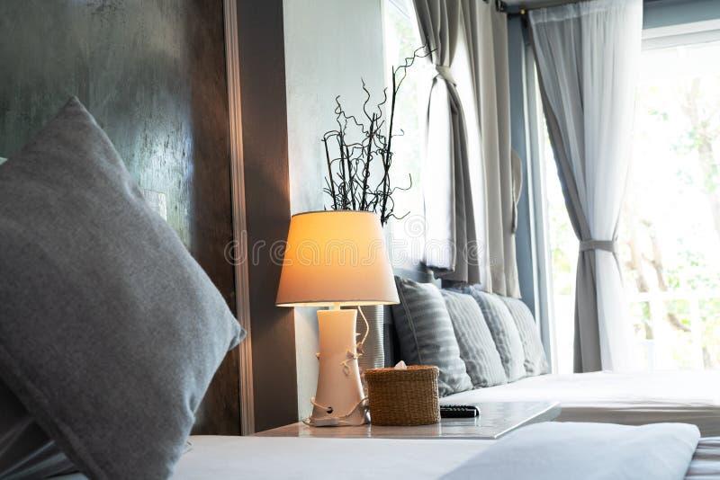 Comfortabele woonkamer, grijze hoofdkussen en bureaulamp stock afbeelding