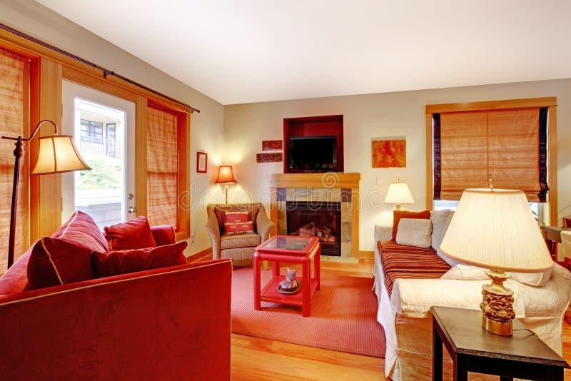 Comfortabele woonkamer met rode bank en open haard stock afbeeldingen