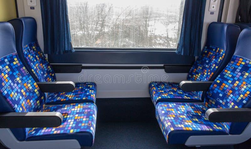 Comfortabele zetels in leeg treincompartiment met venster Modern treinbinnenland royalty-vrije stock fotografie