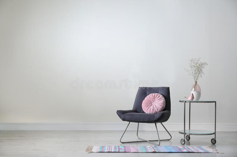 Comfortable armchair with flowers on table near beige wall. Stylish room interior stock photos