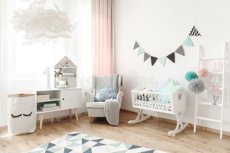 Comfortable armchair in bedroom. Comfortable armchair standing in the corner of a scandi style kid`s bedroom interior stock photo