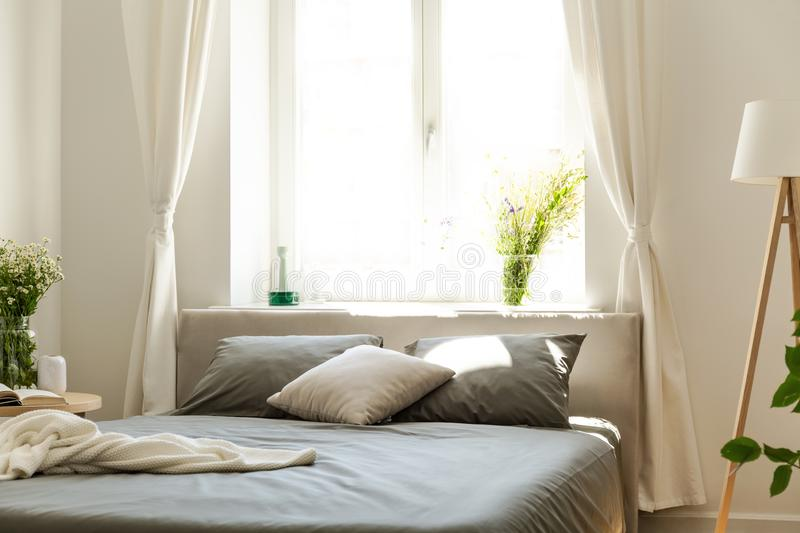 A comfortable bed with graphite bedding and cushions against a bright window in an eco friendly bedroom interior in a tenement hou. Se in woods. Real photo stock photography