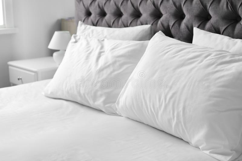 Comfortable bed with white linen and pillows royalty free stock photo