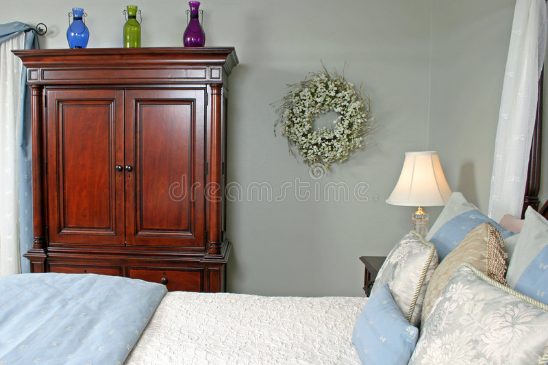 Comfortable Bedroom. A view of a well decorated bedroom with a cherry dresser royalty free stock images