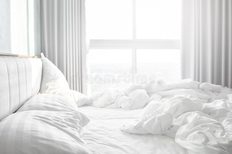 Comfortable bedroom,messy bedding sheets and duvet with wrinkle messy in the bedroom.  stock photo