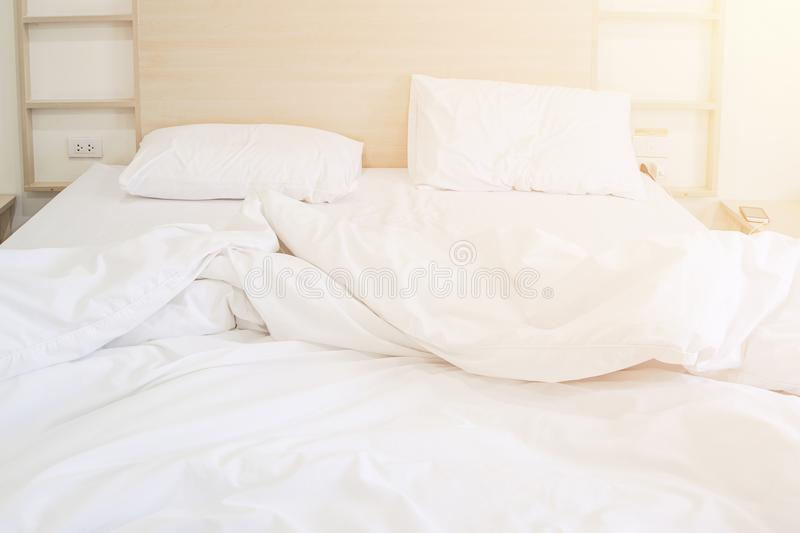 Comfortable bedroom unmade white bedsheet messy and pillow after sleep with sun light in the morning effect stock photos