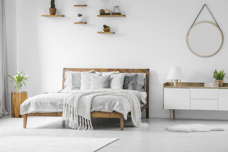 Comfortable big wooden framed bed with linen, pillows and blanket, nightstand beside and round mirror hanging on a white wall in stock images