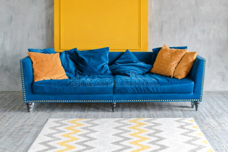 Comfortable classic blue couch with orange pillows in simple minimalist apartment. stock photo
