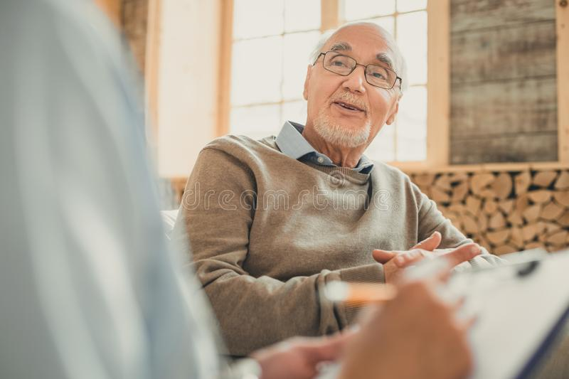 Bald senior in cozy sweater talking with his doctor. Comfortable conversation. Bald senior in cozy sweater talking with his doctor looking relaxed and chill royalty free stock images