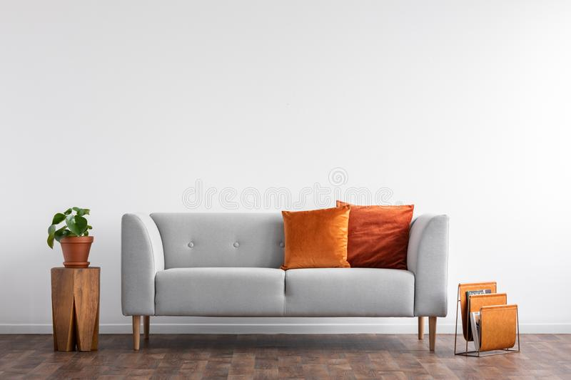 Comfortable couch with orange and red pillow in spacious living room interior,. Real photo with copy space on the empty white wall royalty free stock photography