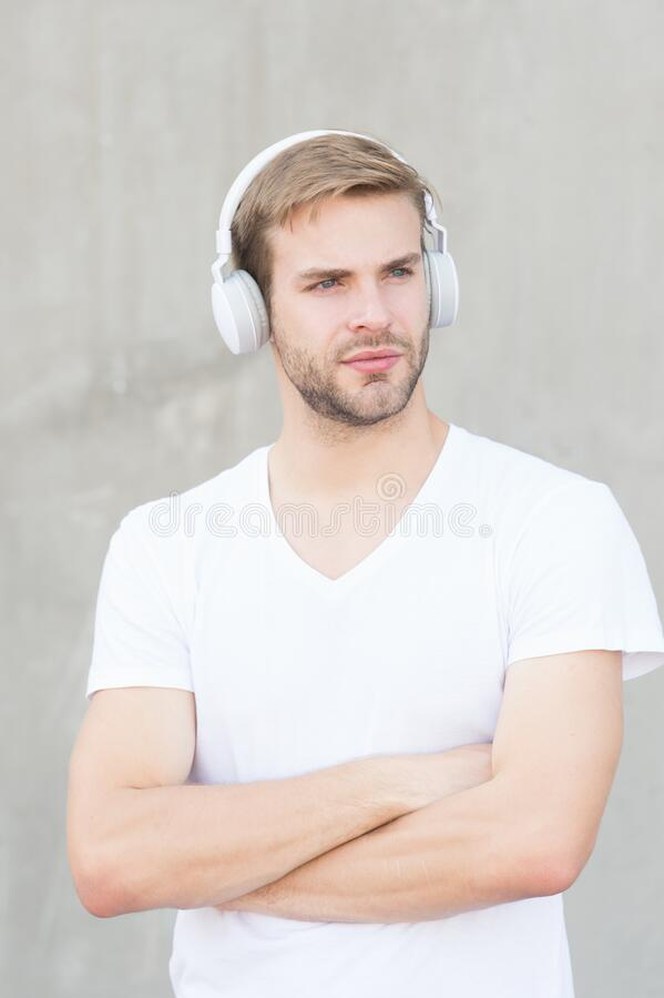 Comfortable ergonomic design. Modern guy wear headphones grey background. Handsome man listen to modern music. Modern. Music technology. Modern and contemporary royalty free stock images
