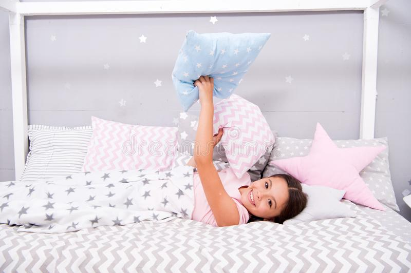 Comfortable pillow. Girl smiling child lay bed star pattern pillows and plaid bedroom. Bedclothes for children. Girl kid stock photo