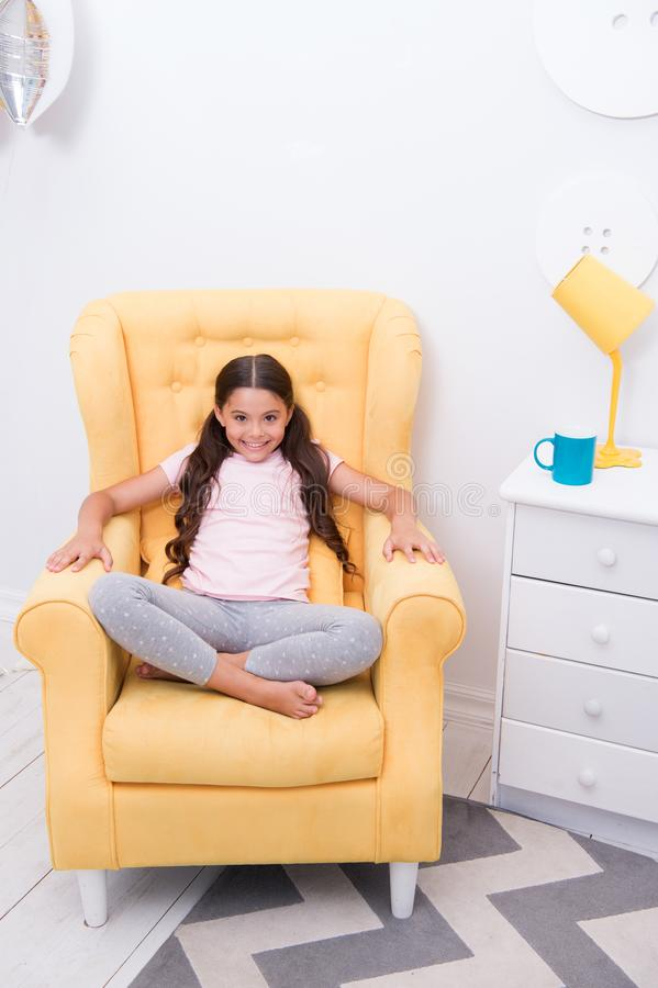 Comfortable place to rest. Girl cute kid sit yellow chair fashionable pajamas. Child girl ready go to bed. Girl smiling royalty free stock images