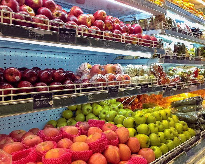Comfortable shelves in grocery store with apples of different varieties and colors. In background vegetables in blurred perspective stock images