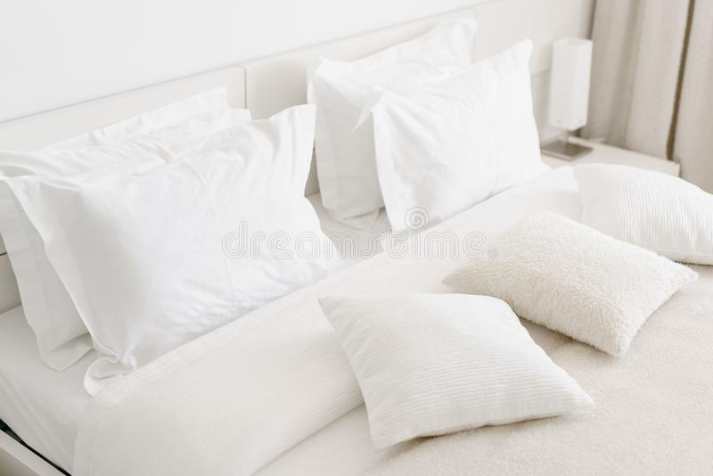 Comfortable soft pillows on the bed. Close-up white bedding sheets and pillow on light wall room background. Fresh bed. Comfortable soft pillows on the bed stock photography
