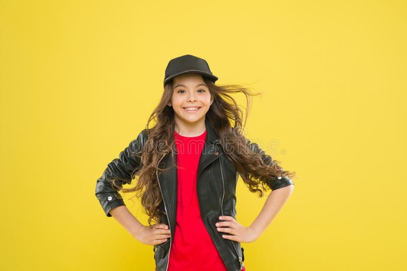 Comfortable style. Adorable stylish girl smiling on yellow background. Stylish look of small fashion model. Happy little. Child with cute smile in stylish royalty free stock images