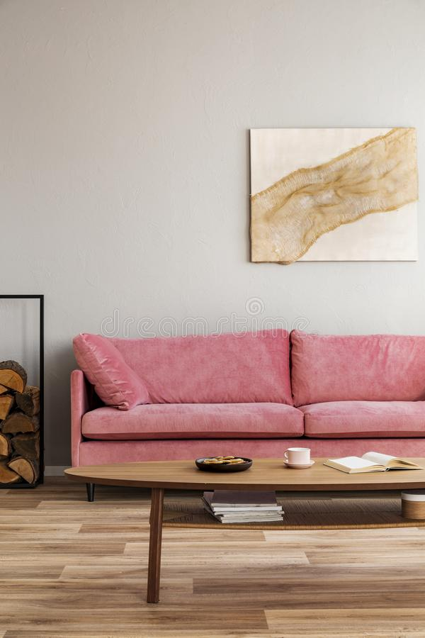 Comfortable velvet pastel pink couch in elegant beige interior with abstract painting stock image