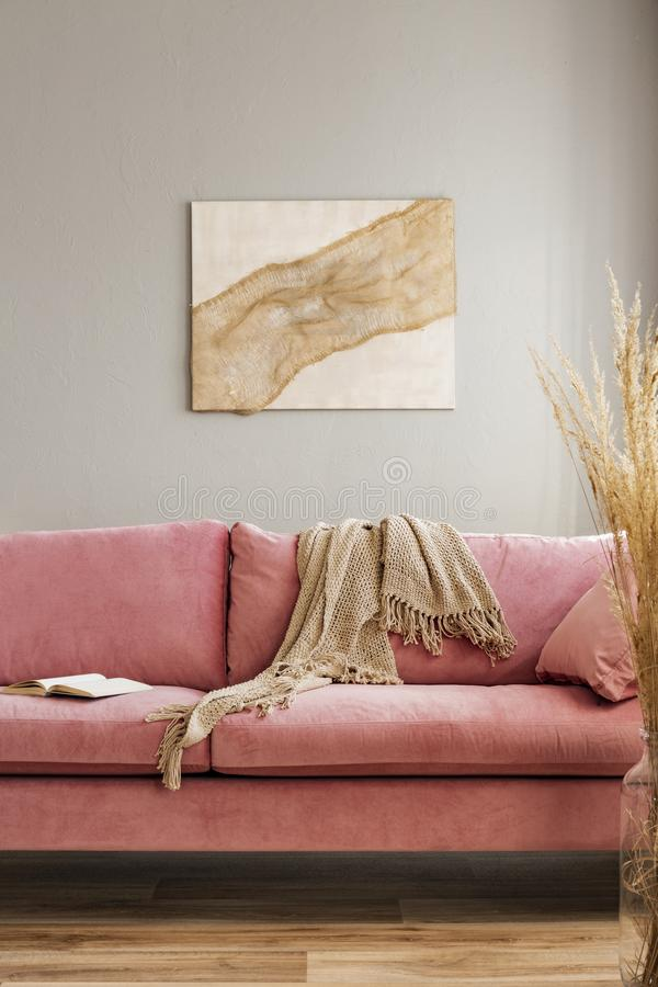 Comfortable velvet pastel pink couch in elegant beige interior with abstract painting stock photo