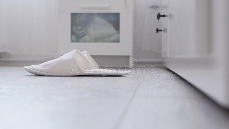 Comfortable White and Fluffy Slippers Waiting in Front of Bed in Bedroom royalty free stock image