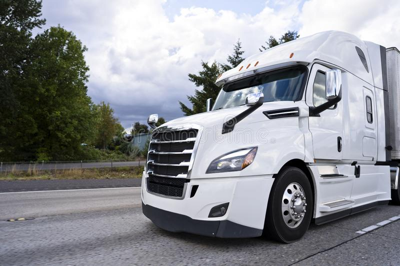 Comfortable white modern big rig semi truck running on divided h. Comfortable white modern bonnet big stylish professional rig semi truck running on divided stock photos