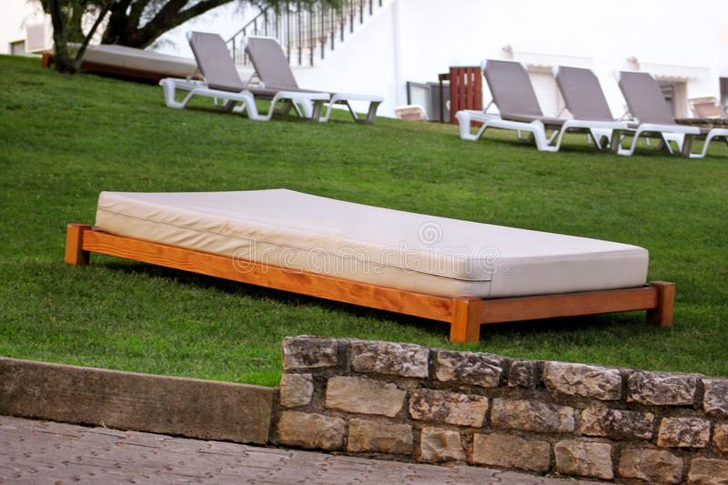 Comfortable white sun beds for sunbathing on grass, relax in tropical garden of luxury resort hotel. Exotic beach on sea. stock photography