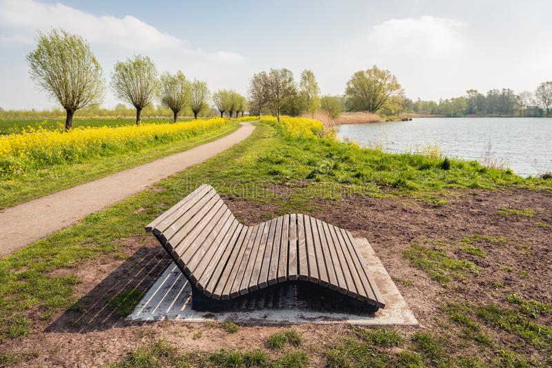 Comfortable wooden slat bench recently installed in a park. Comfortable wooden slat bench in a Dutch park near the village of Wagenberg, North Brabant. It is royalty free stock photo