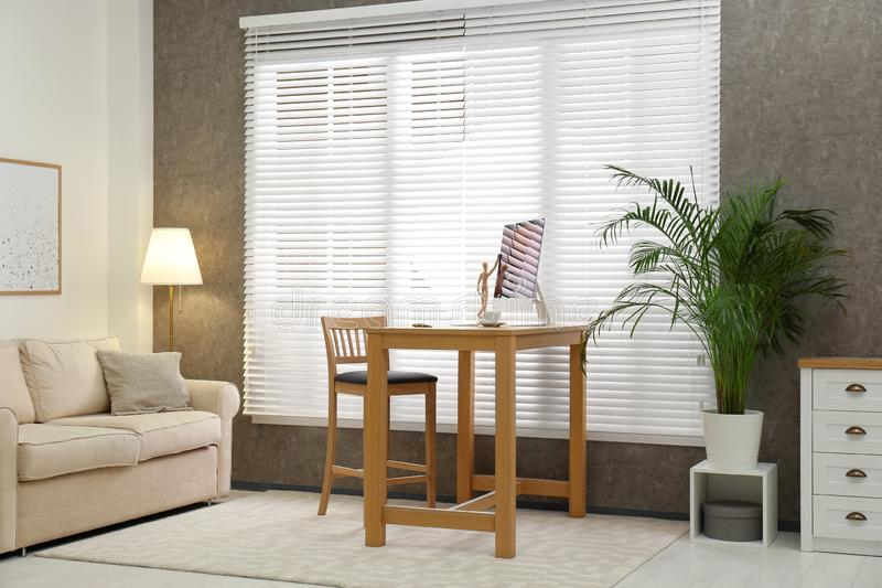 Comfortable workplace  window with blinds in room. Comfortable workplace near window with blinds in room royalty free stock images